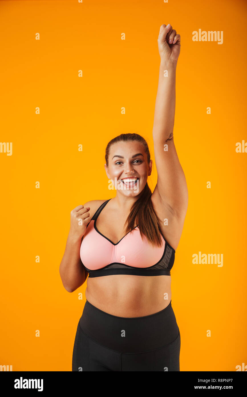 6f02cbba3748a Portrait of young chubby woman in sportive bra smiling and standing isolated  over yellow background -