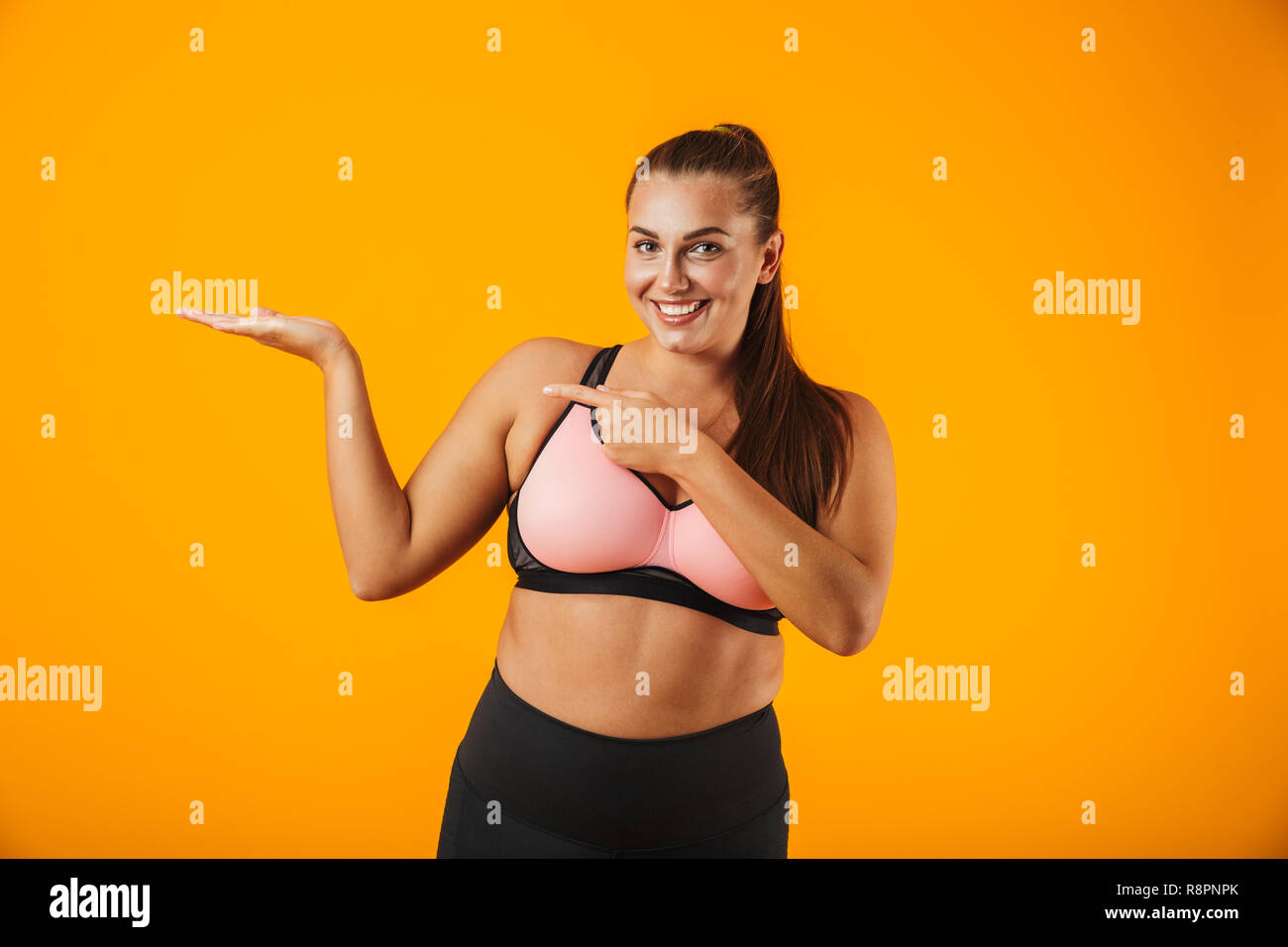 0a61c36ed0 Portrait of european chubby woman in sportive bra holding copyspace on palm  isolated over yellow background