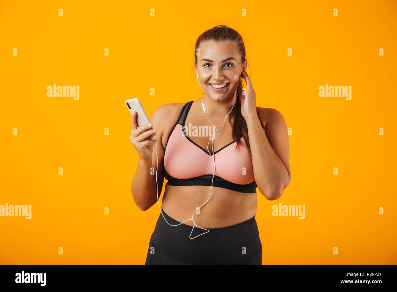 a5b48361667b2 Portrait of smiling chubby woman in sportive bra listening to music with  earphones and smartphone isolated over yellow background