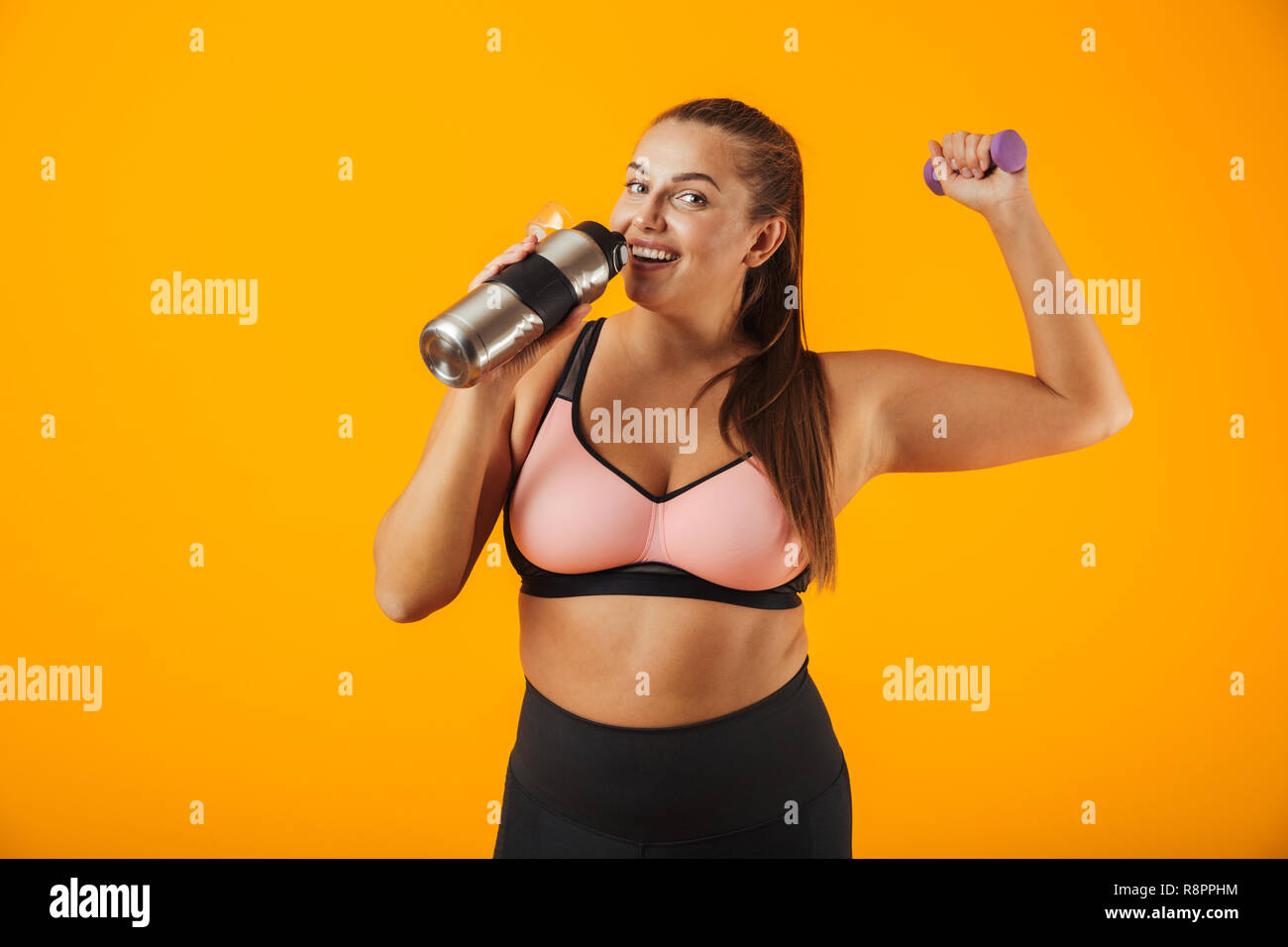 c7f5756f57 Portrait of young chubby woman in sportive bra drinking water from thermos  while lifting dumbbell isolated over yellow background