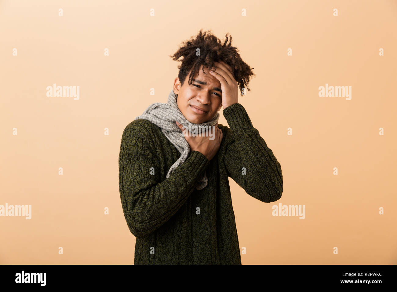 Portrait of a young african man dressed in autumn clothes isolated over beige background, suffering from a sore throat - Stock Image