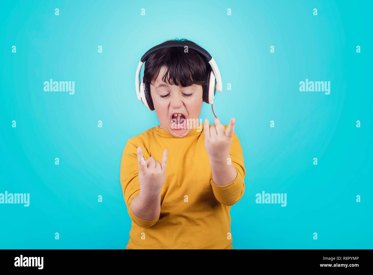 Boy with headphones showing rock sigh on blue background - Stock Image
