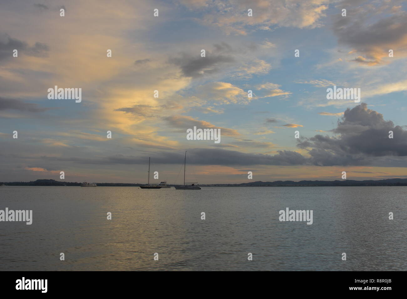 Calm surface of Waitemata Harbour reflecting sun light with moored sailing boats and distant land in background in cloudy evening. - Stock Image