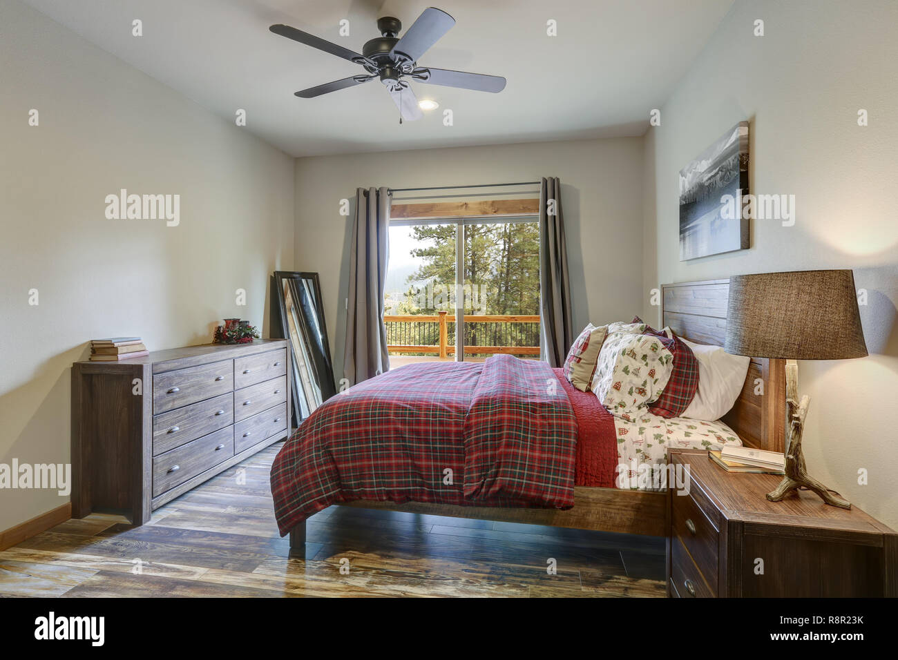 Restful Country Bedroom Furnished With Wooden Master Bed Dark Gray Dresser And View Of Spacious Deck Stock Photo Alamy