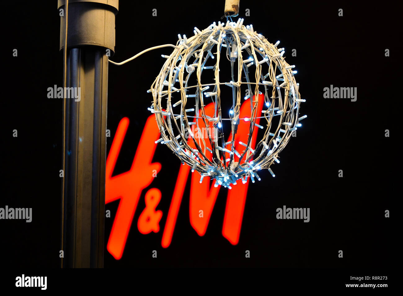 Nis,Serbia,December 24,2016:decorative big ball made of Christmas lights in front of H&M logo by night on street for holidays. - Stock Image
