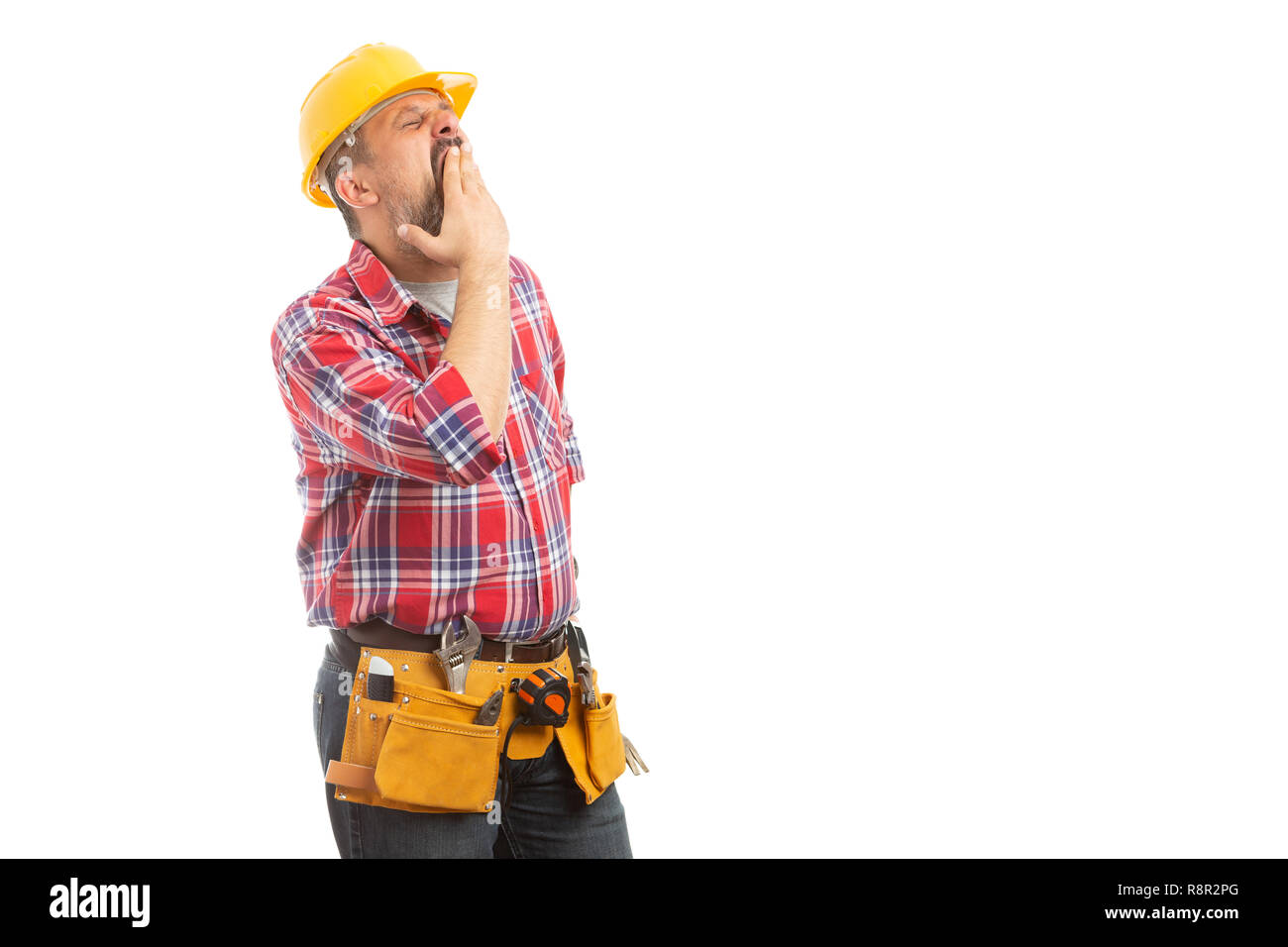 Sleepy builder covering mouth while yawning as tiresome hard work isolated on white studio background - Stock Image