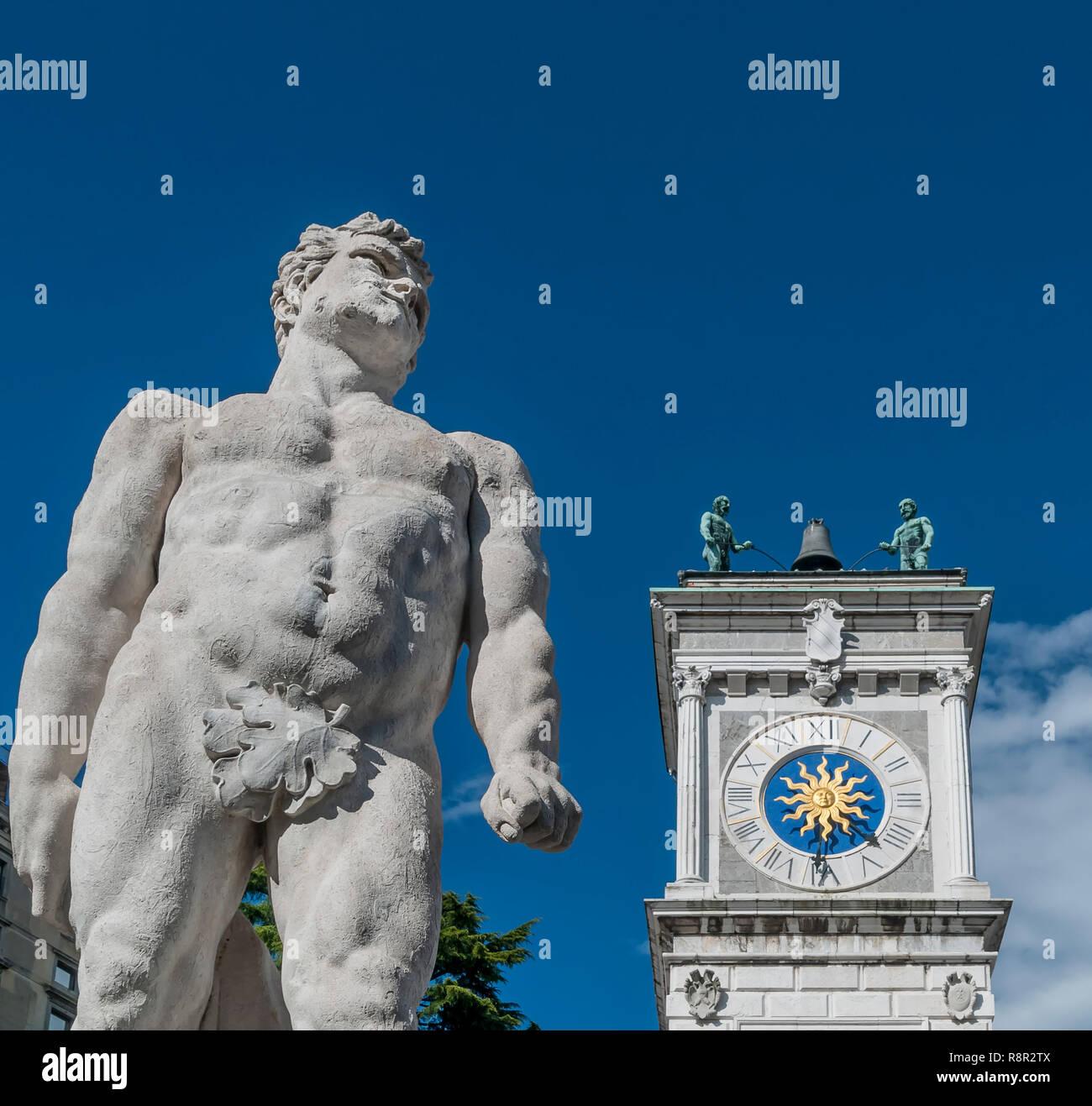 The statue of Hercules with the clock tower of the San Giovanni colonnade, Piazza della Libertà, Udine, Friuli, Italy - Stock Image