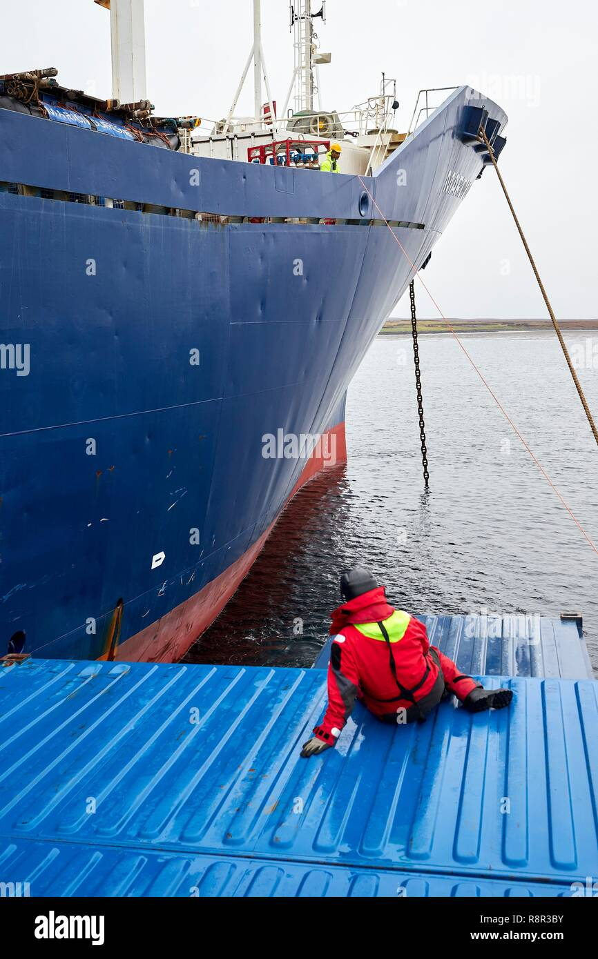 France, French Southern and Antarctic Lands, Kerguelen Islands, Port-aux-Français, on board the barge Aventure II, the only boat of the island, which transports the heavy freight (container) between the Marion Dufresne and the pier of Port-aux-Français. A seaman sitting on a container during the approach of the Marion Dufresne - Stock Image