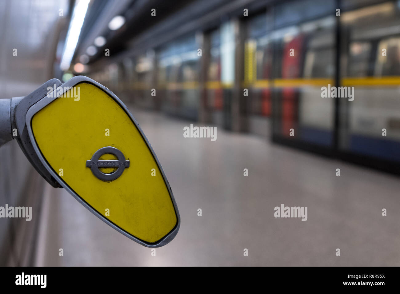 In foreground, end of handrail at Southwark underground station, London showing TFL roundel. In background blurred train arrives on the platform. - Stock Image