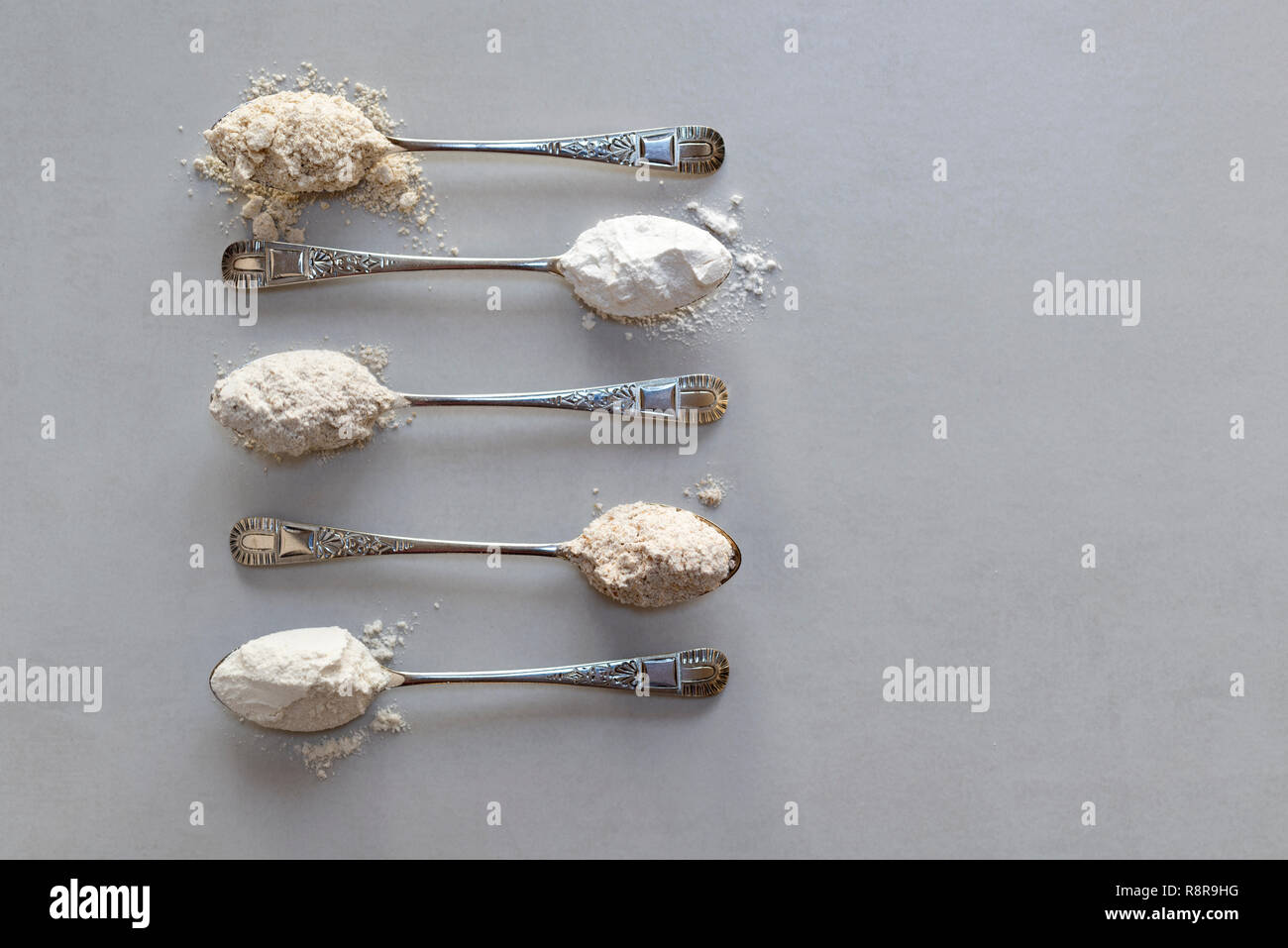 Five spoonfuls of different flours. From the top: oat flour, rice flour, rye flour, wholewheat flour, plain flour. - Stock Image
