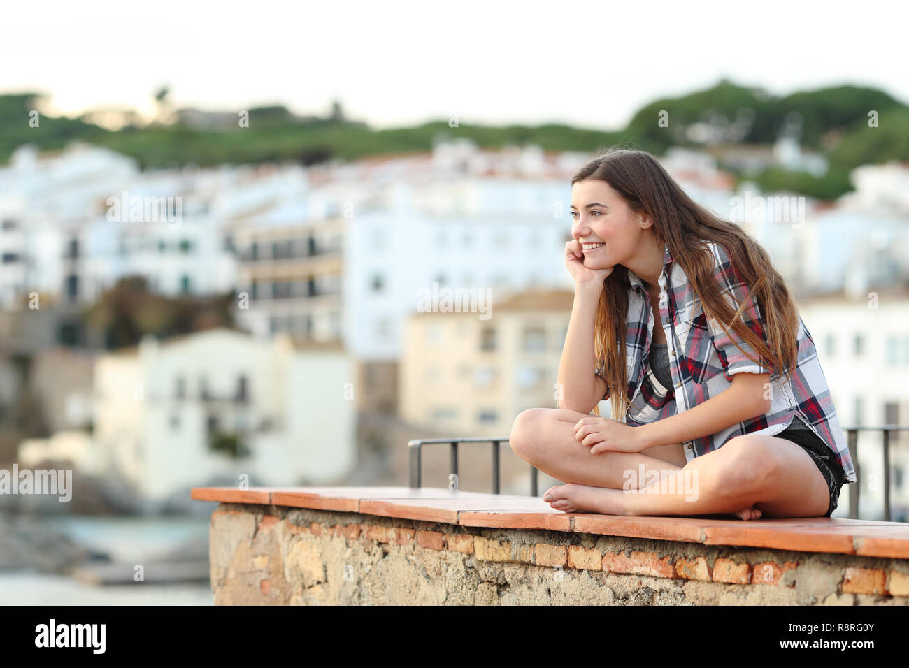 Pensive happy teenage girl contemplating hozizon sitting on a ledge in a coast town - Stock Image