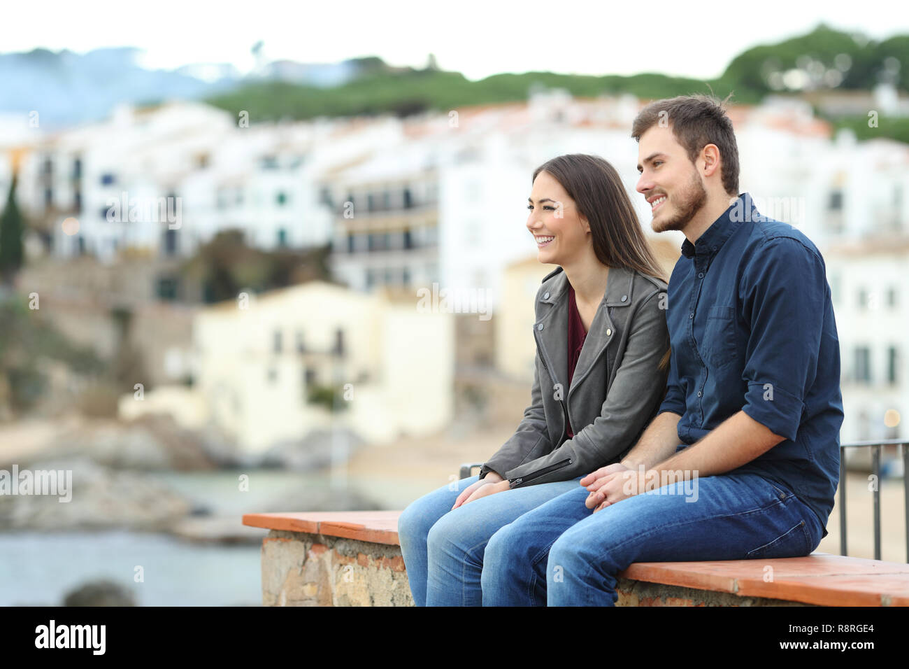 Happy couple or friends looking away on vacation sitting on a ledge in a coast town - Stock Image