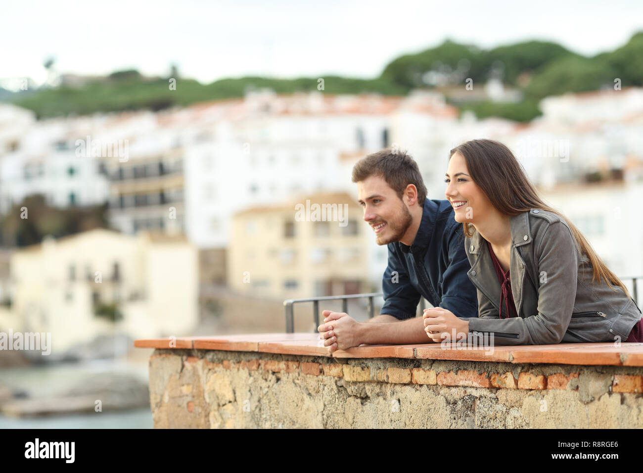 Happy couple contemplating views from a balcony on vacation in a coast town - Stock Image