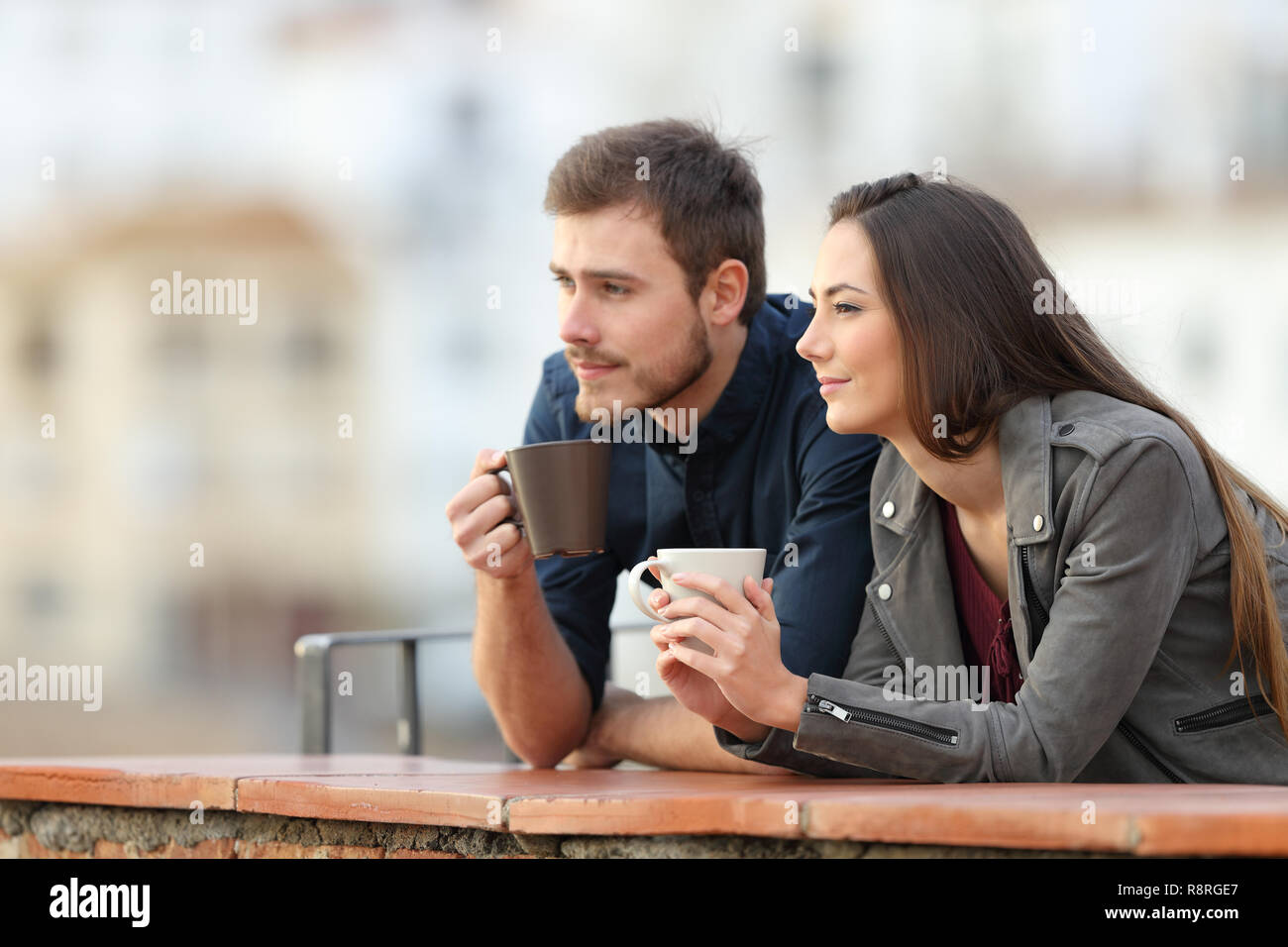 Happy couple relaxing drinking coffee in a balcony looking away on vacation - Stock Image