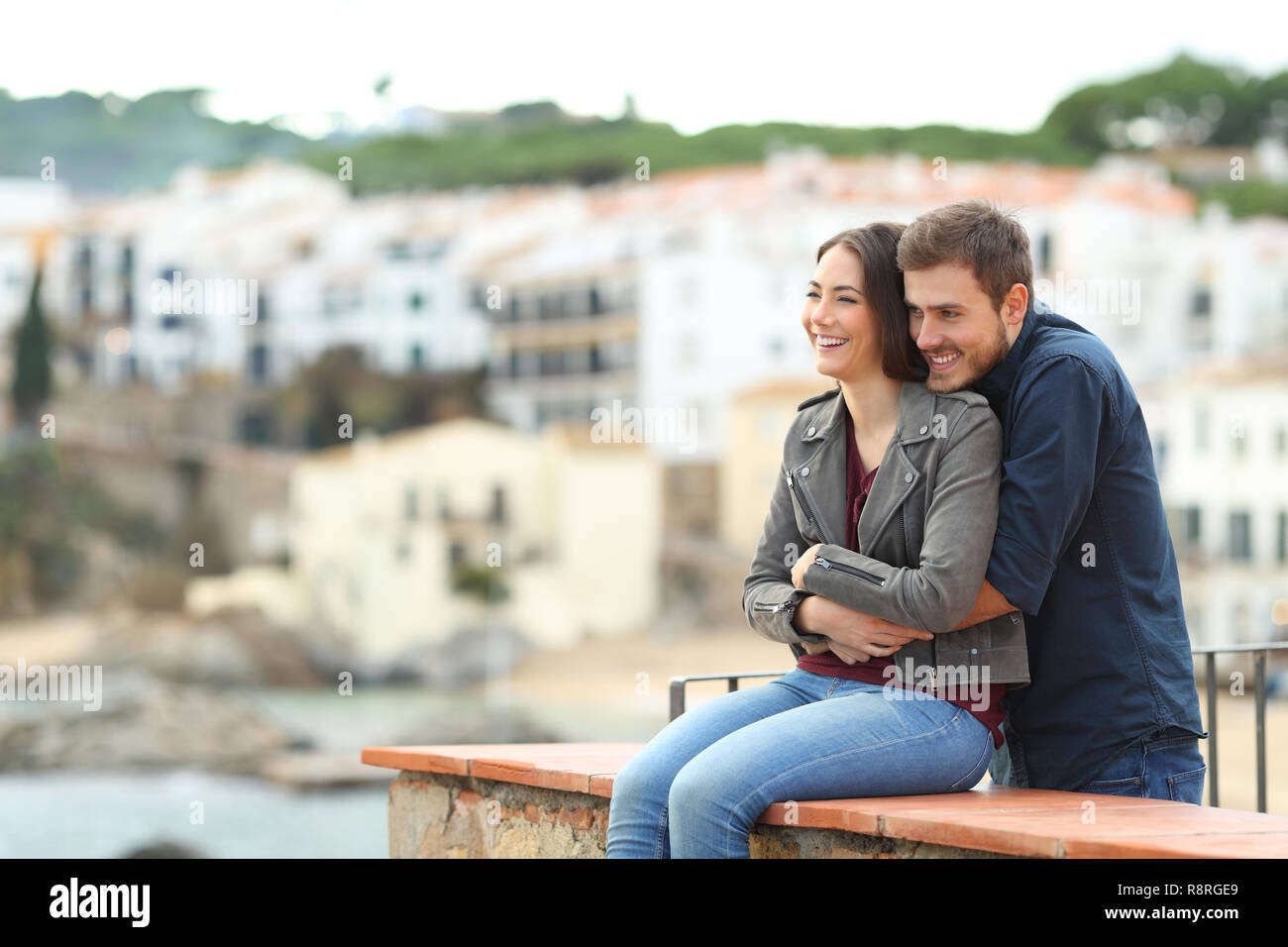 Happy couple in love embracing looking away in a coast town on vacation - Stock Image