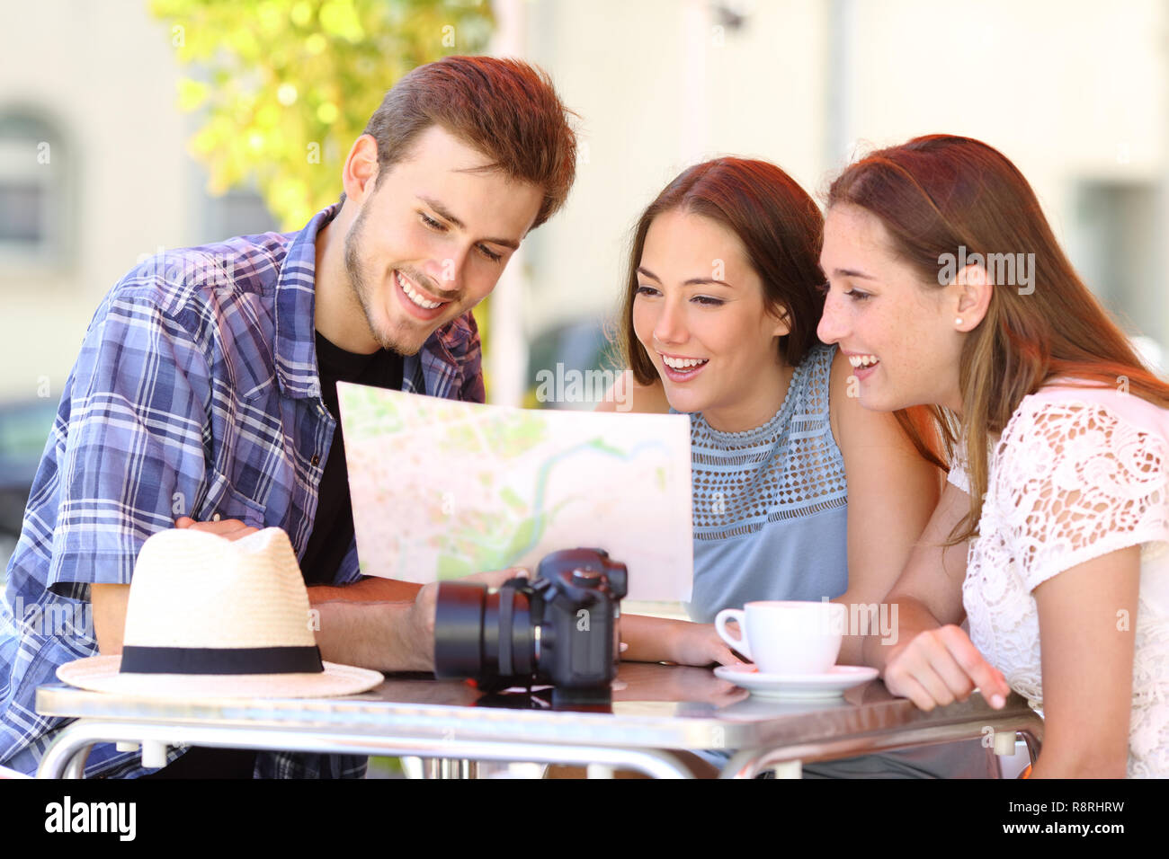 Three happy tourists planning travel consulting a paper guide in a bar terrace - Stock Image