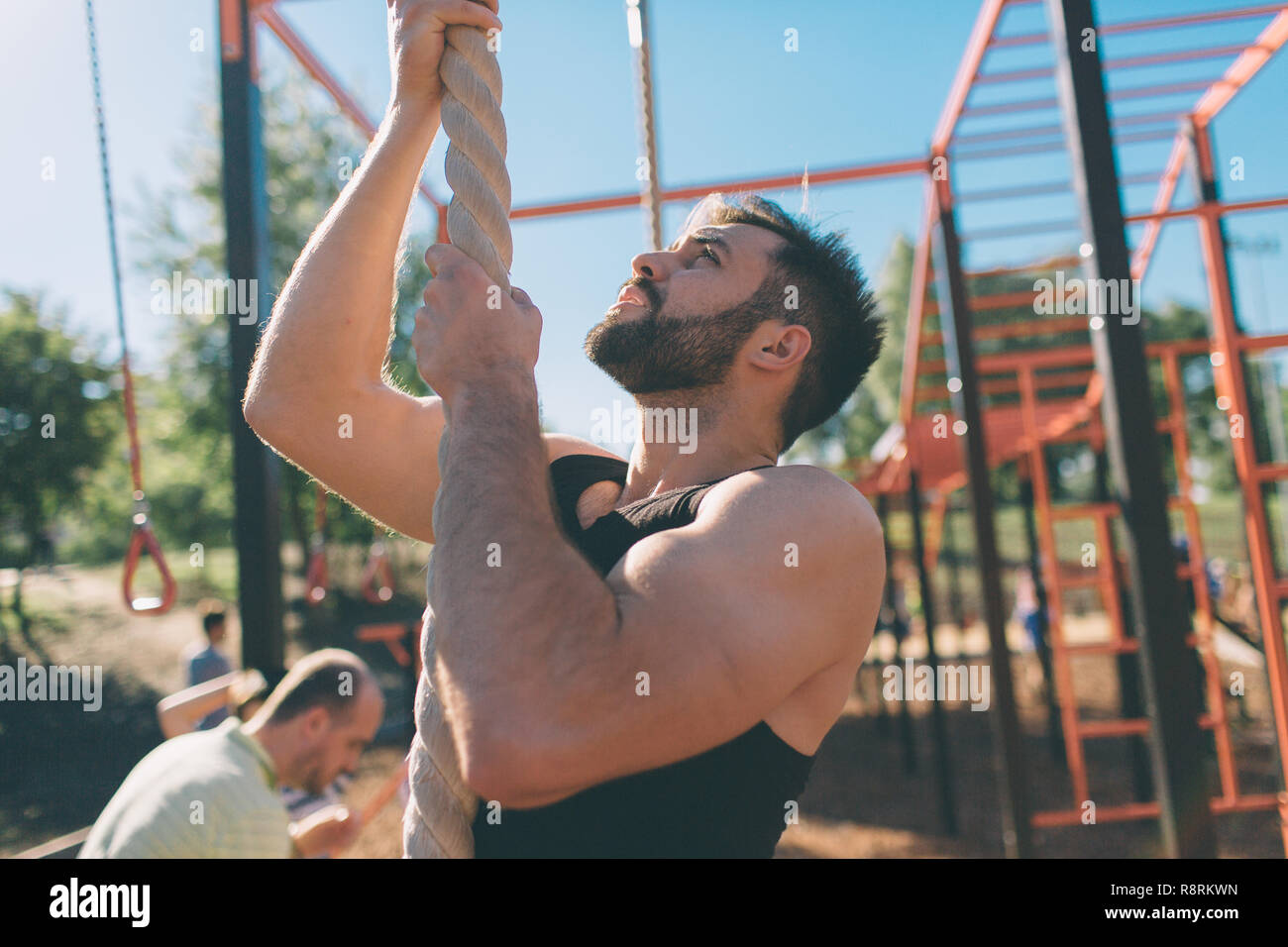Bearded with black hair man climbing thick rope during fitness exercises in cross-fit training with. Strong muscular hands. - Stock Image