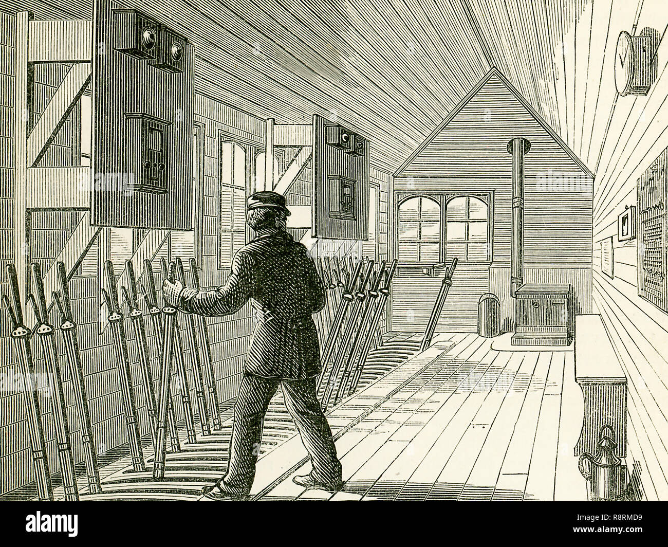 "This illustration dates to the 1870s and shows the signal box on the North London Railway. The interior of a signal-box near an important junction or station is shown here, and we see here the numerous levers for working the points and the signals, each of these having a connection, by rods or wires, with the corresponding point or signal-post. The electric telegraph is now an important agent in railway signalling, and in a signal-box we may see the bells and instruments which inform the pointsman whether a certain section of the line is ""blocked"" or ""clear."" The signals now generally used on  - Stock Image"