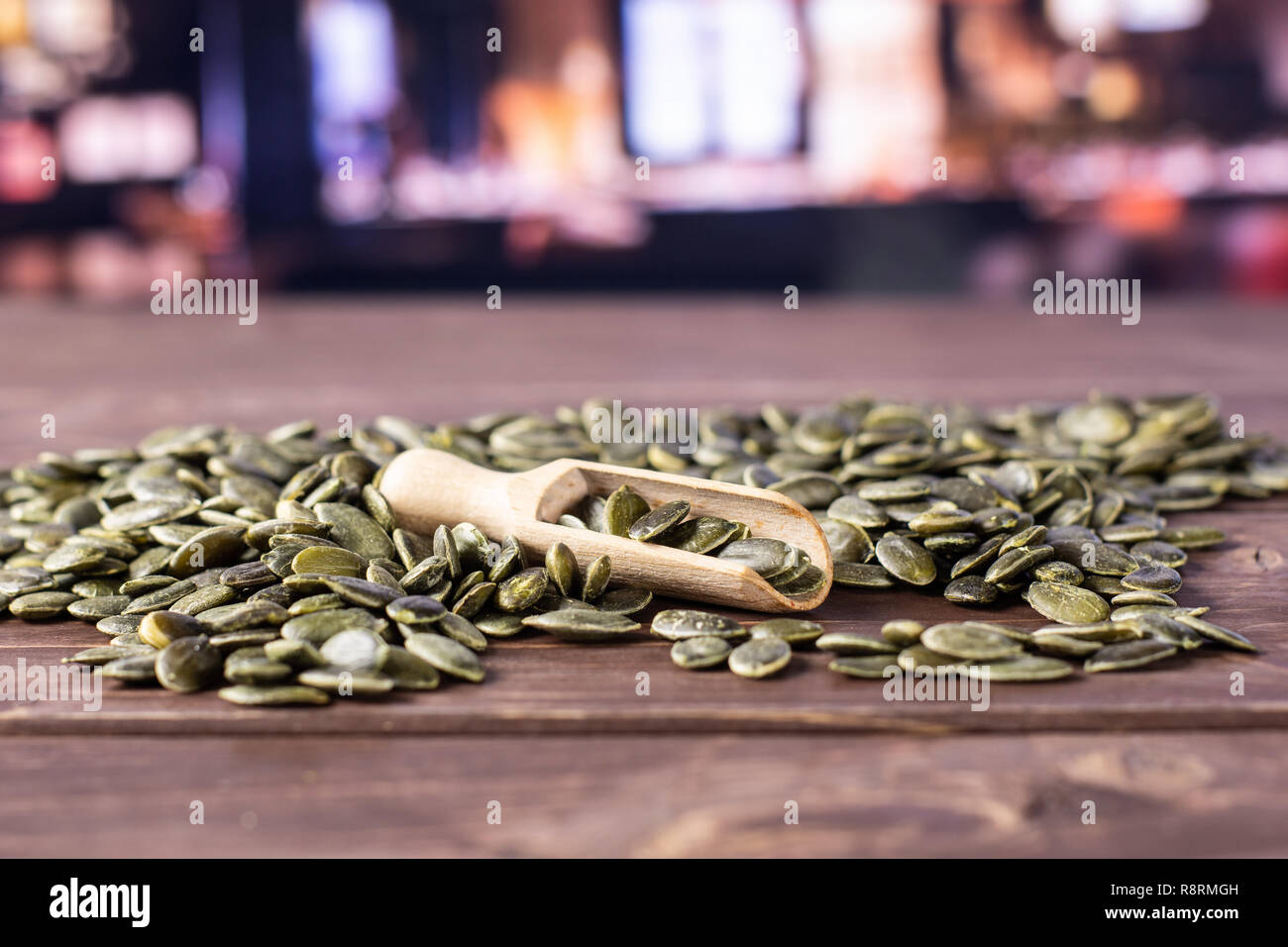 Lot of whole hulled pumpkin seeds with wooden scoop with restaurant in background Stock Photo