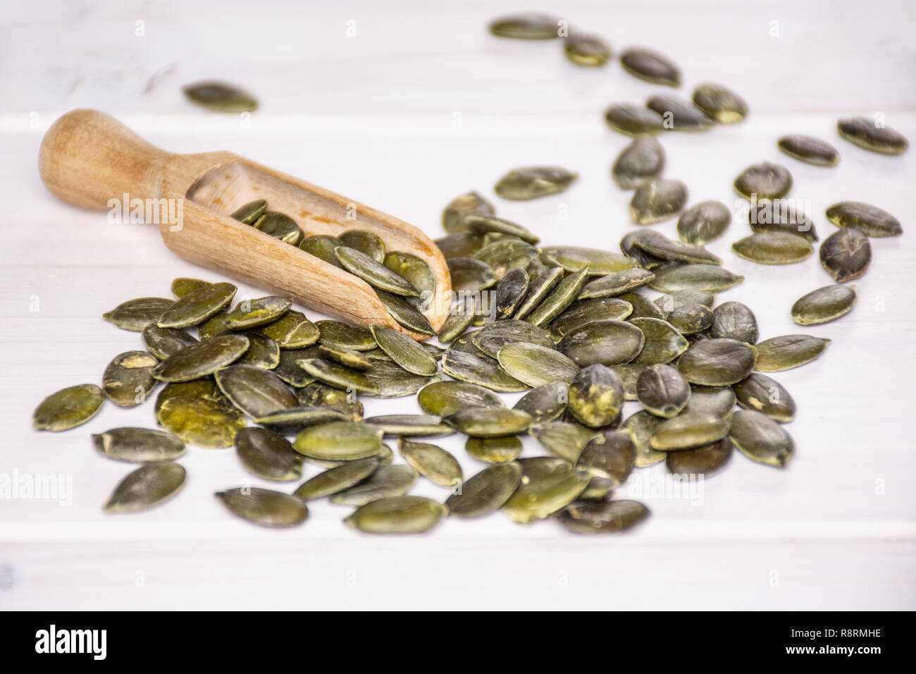 Lot of whole hulled pumpkin seeds with wooden scoop on white wood Stock Photo