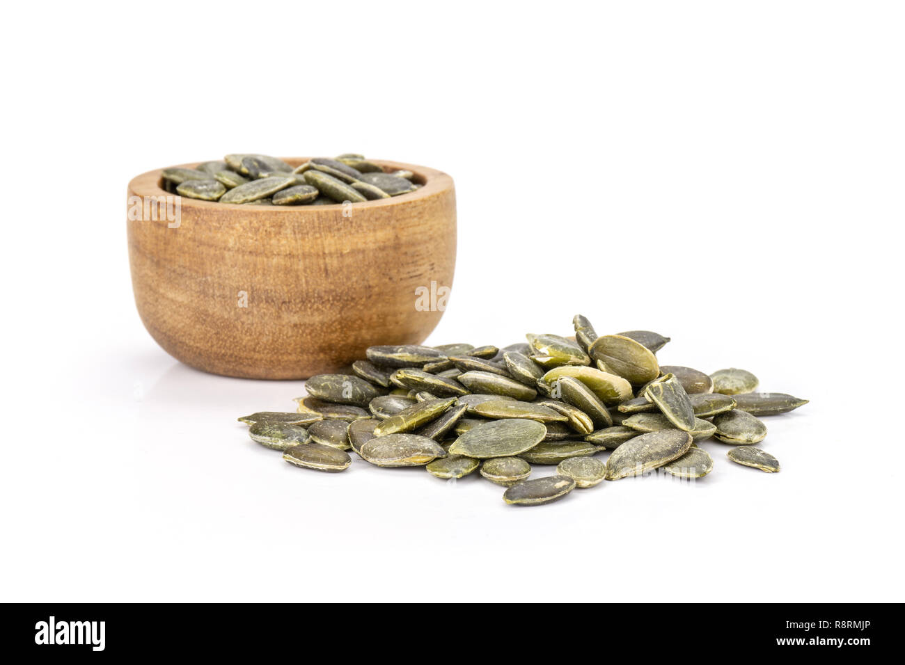 Lot of whole hulled pumpkin seeds heap with wooden bowl isolated on white background Stock Photo