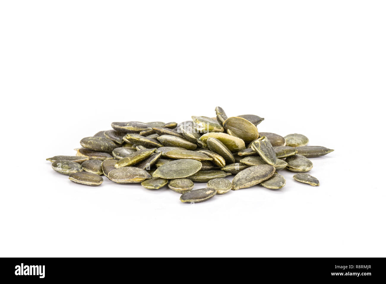 Lot of whole hulled pumpkin seeds heap isolated on white background Stock Photo
