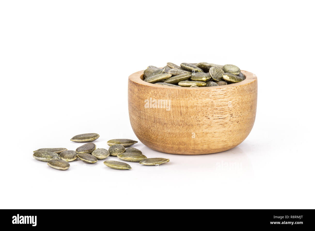 Lot of whole raw hulled pumpkin seeds with wooden bowl isolated on white background Stock Photo