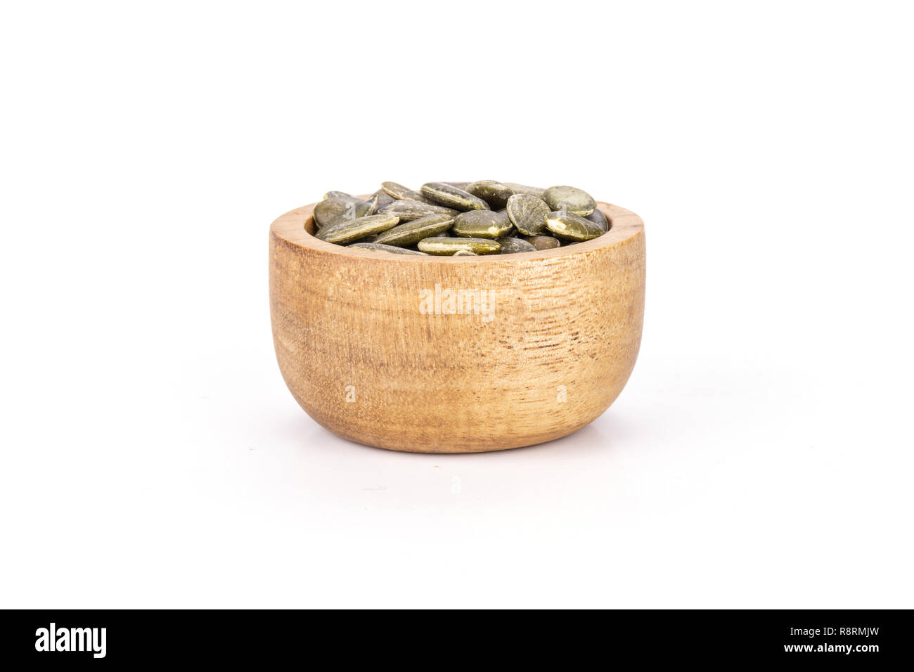 Lot of whole hulled pumpkin seeds with wooden bowl isolated on white background Stock Photo