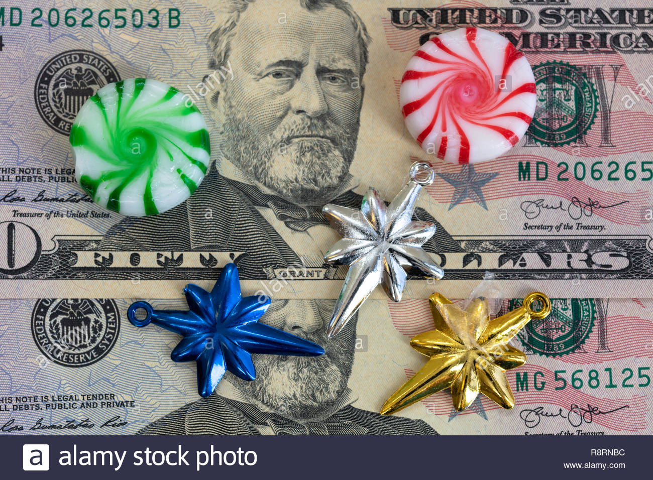 Christmas food and decoration small objects over a background of USD 50 dollar bills. Conceptual image of the commercialization of Christmas - Stock Image