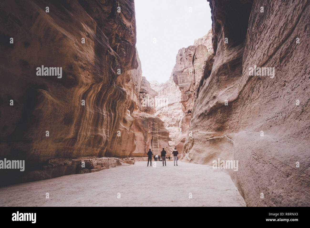 Siq, the narrow slot-canyon that serves as the entrance passage to the hidden city of Petra, Jordan, seen here with tourists walking. UNESCO World Her Stock Photo