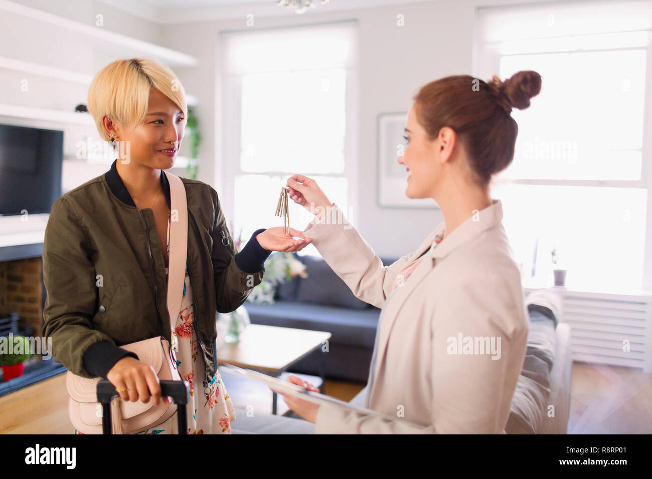 Real estate agent giving house rental keys to young woman - Stock Image