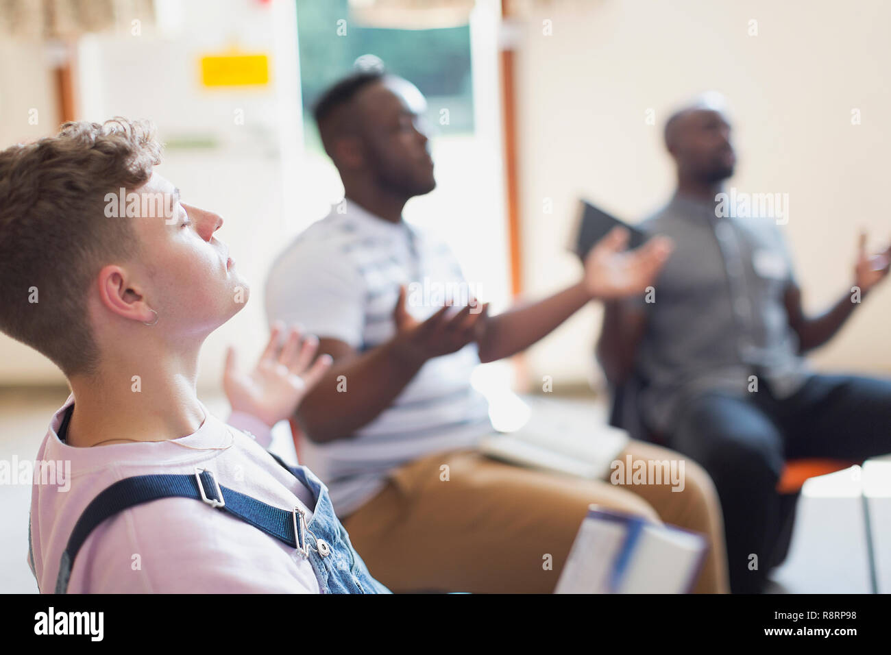 Serene man praying with arms outstretched in prayer group - Stock Image