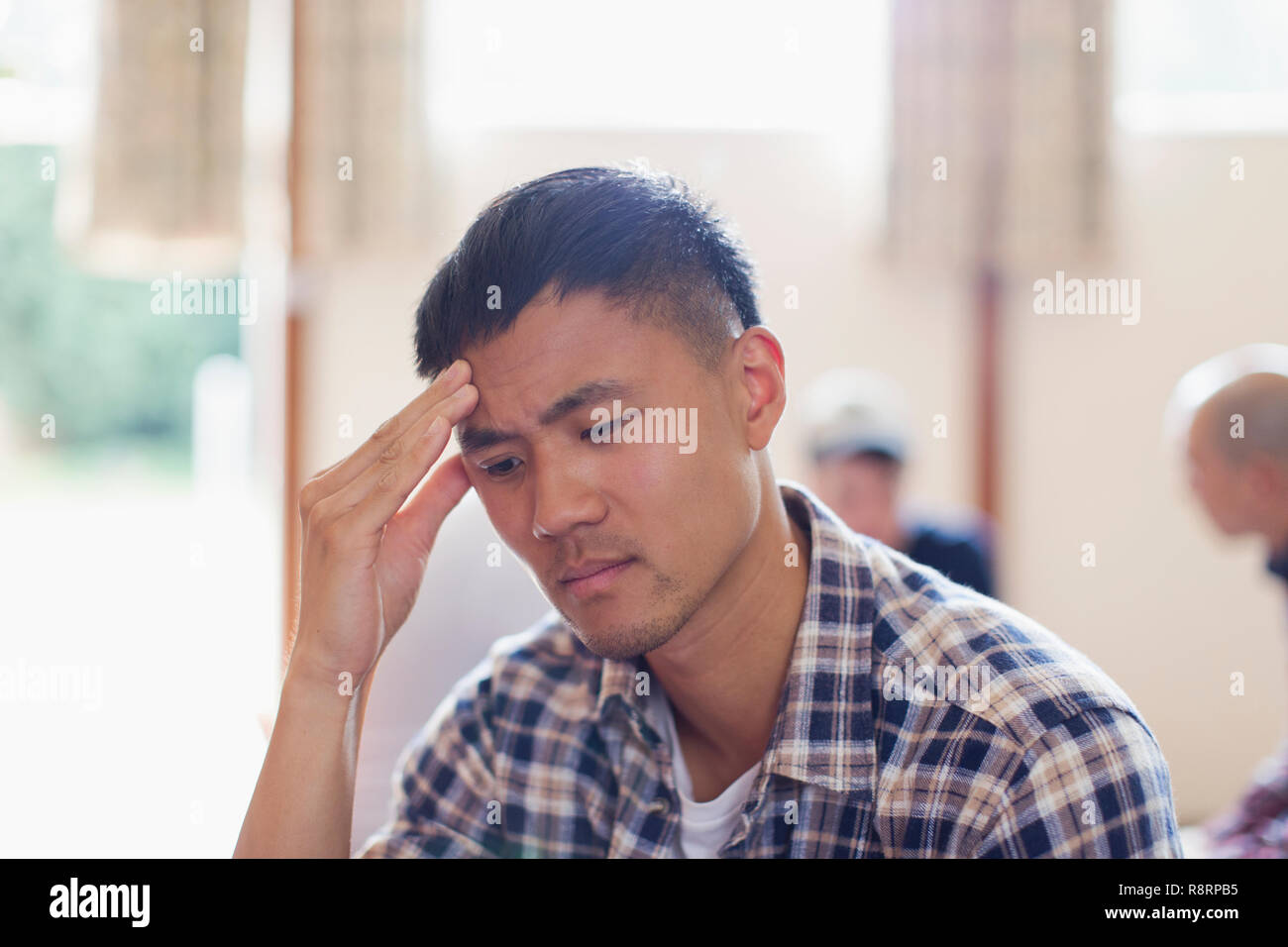 Frustrated man with head in hands - Stock Image