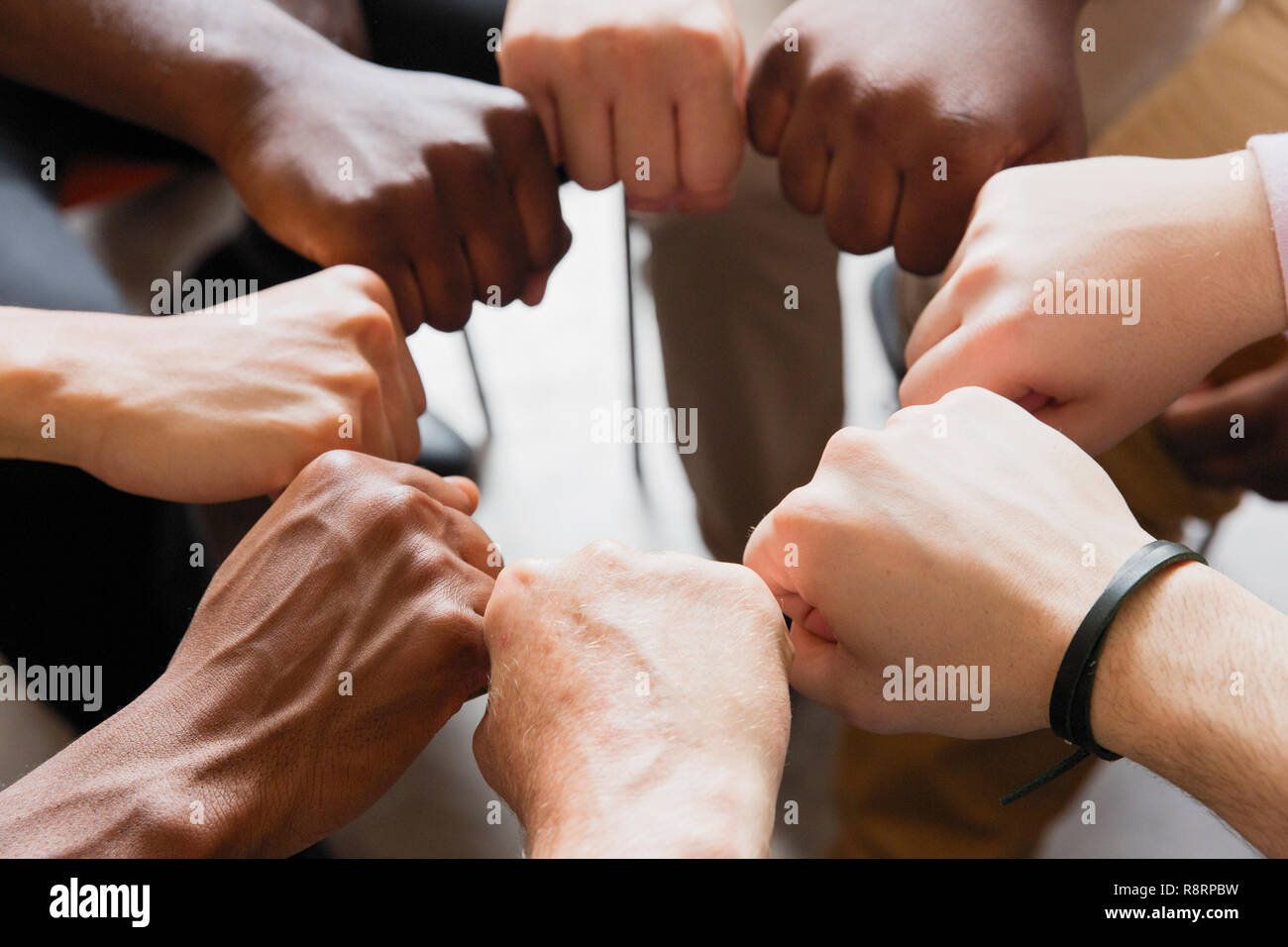 Men joining fists in circle - Stock Image