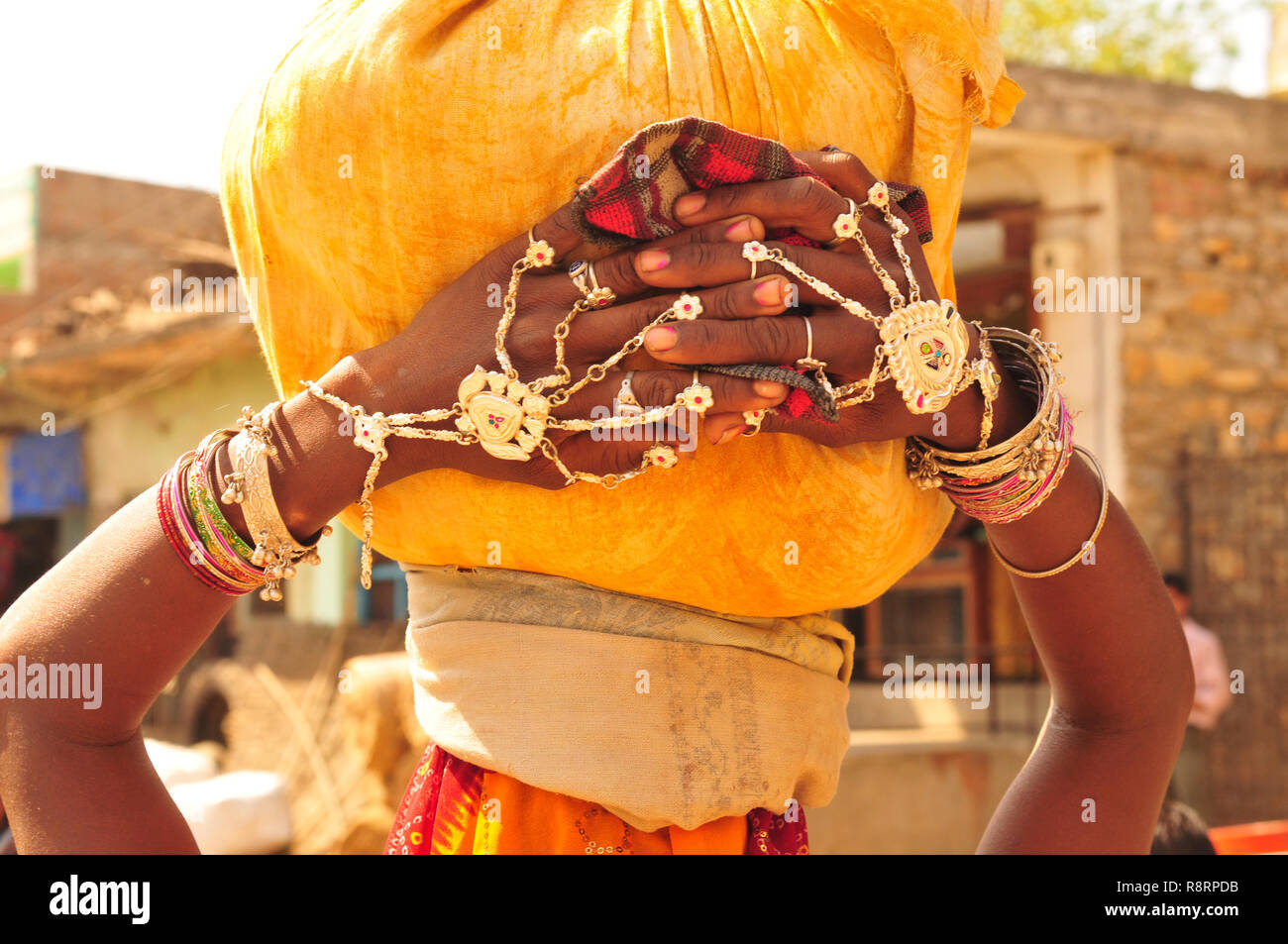 Gujarat: A young woman carring water on her head and showing her bracelets - Stock Image