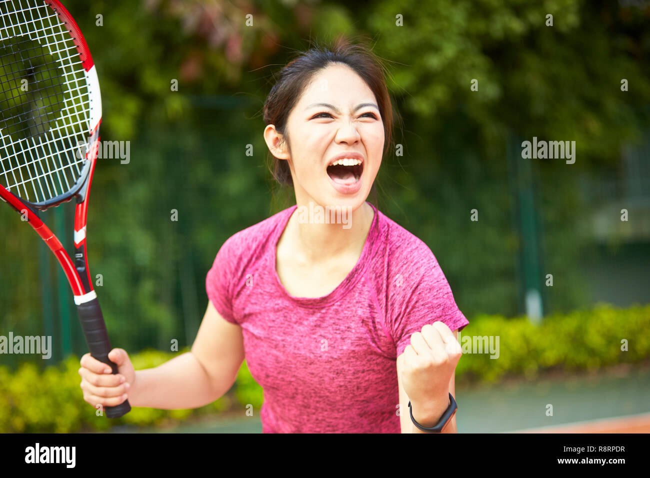 young asian girl female tennis player celebrating after scoring a point Stock Photo