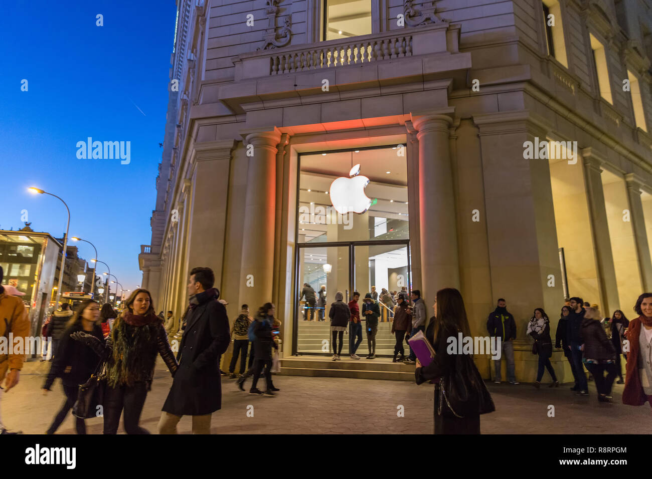 Barcelona, Spain - Dec 10th 2017 - People walking in front of the Apple Store in Barcelona in a cold weather night in Spain - Stock Image