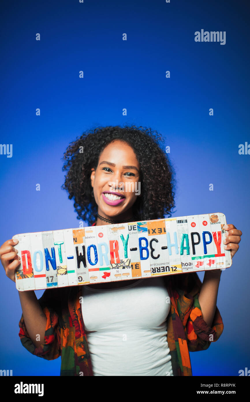 6e165c91d Portrait smiling woman holding Dont Worry Be Happy license plates - Stock  Image
