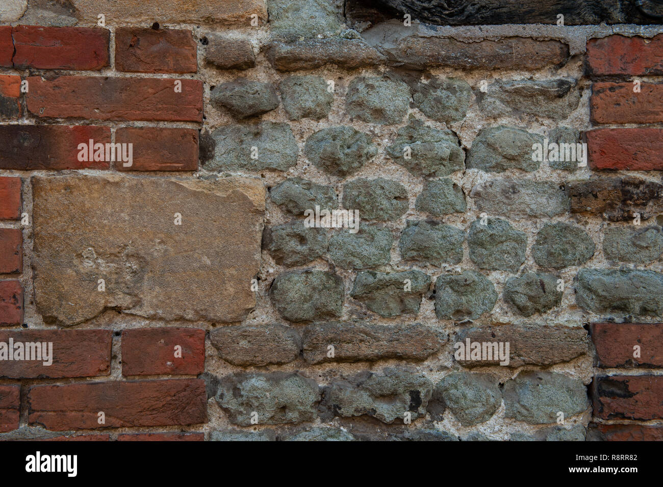 Wall built from mixed material - Stock Image