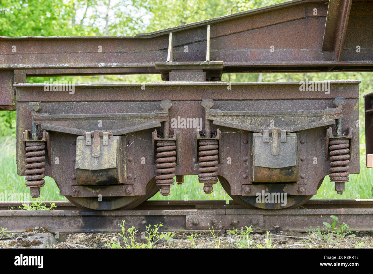 Old train and locomotive wheels. Railroad tracks stretches and green grass and trees. Railway road environment background. Stock Photo