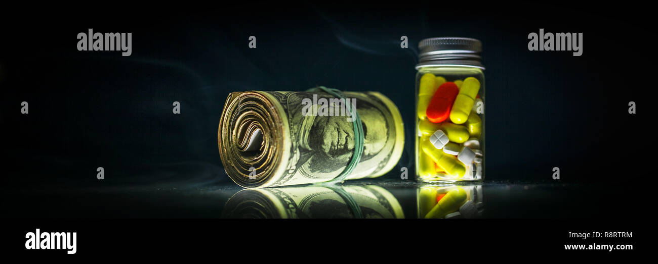 Medicine pills or capsules red, white and yellow, and bunch of money on black background shrouded in smoke with copy space. Drug prescription for trea - Stock Image