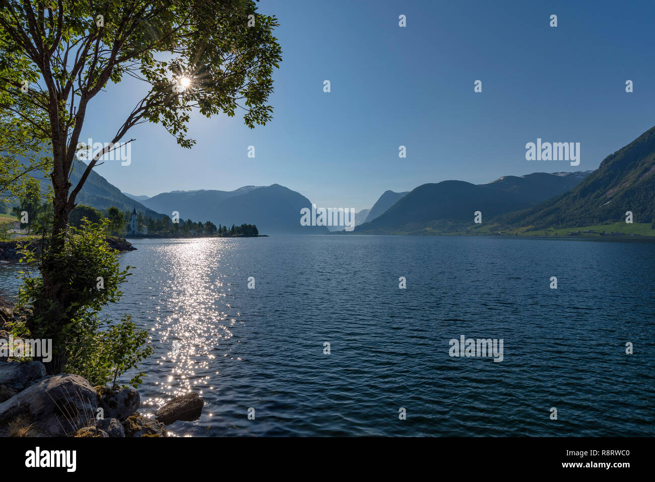 Blue lake surrounded by mountains, green trees under a clean blue sky. Norway, around Alhus. - Stock Image