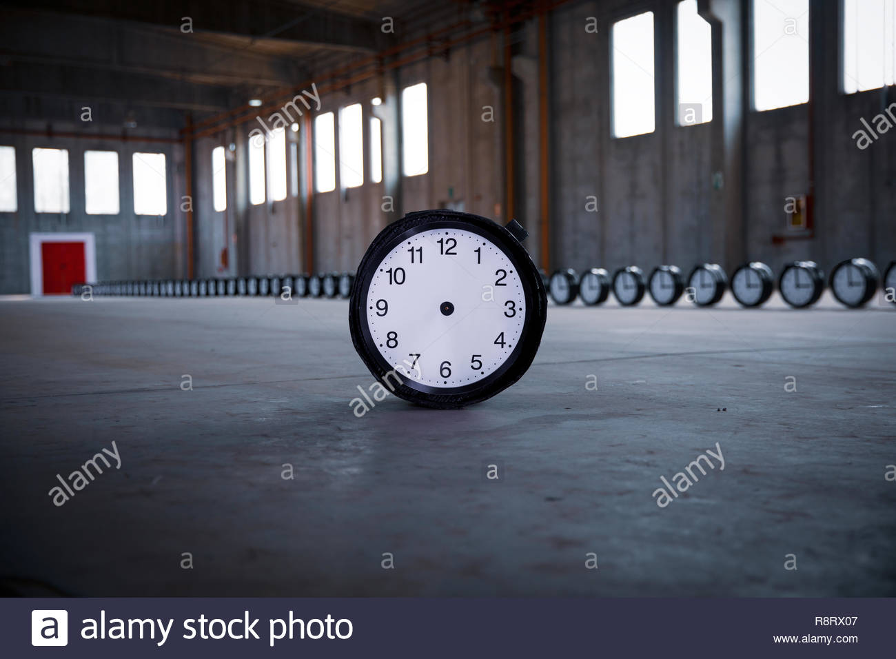 A  clock with no hands stands in the center of the foreground, with 50 identical clocks settled in a row pointing to a red door in an empty factory. - Stock Image