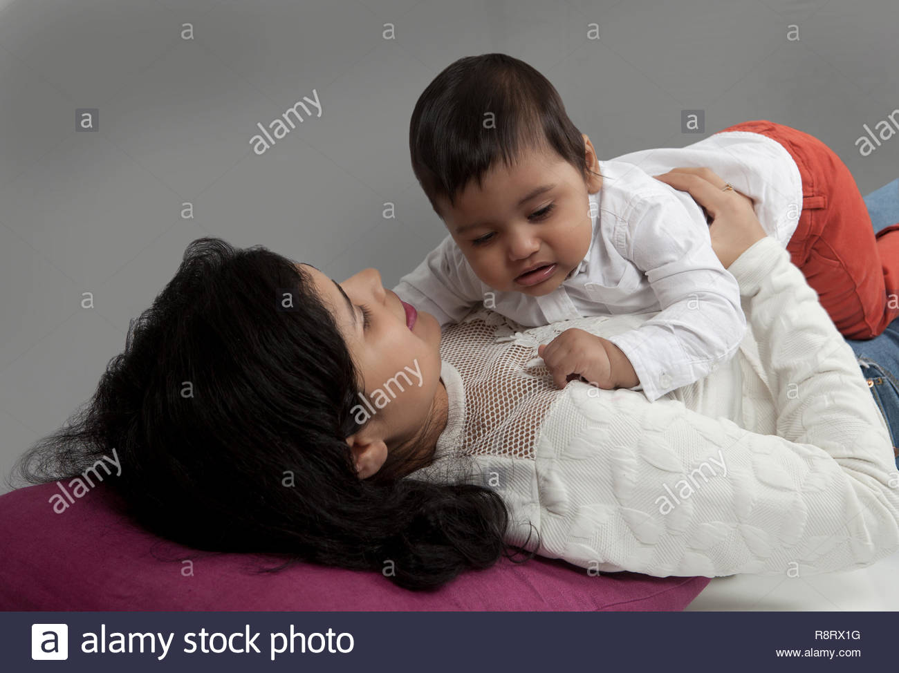 Mother consoling tired or sick baby, trying to make him sleep - Stock Image