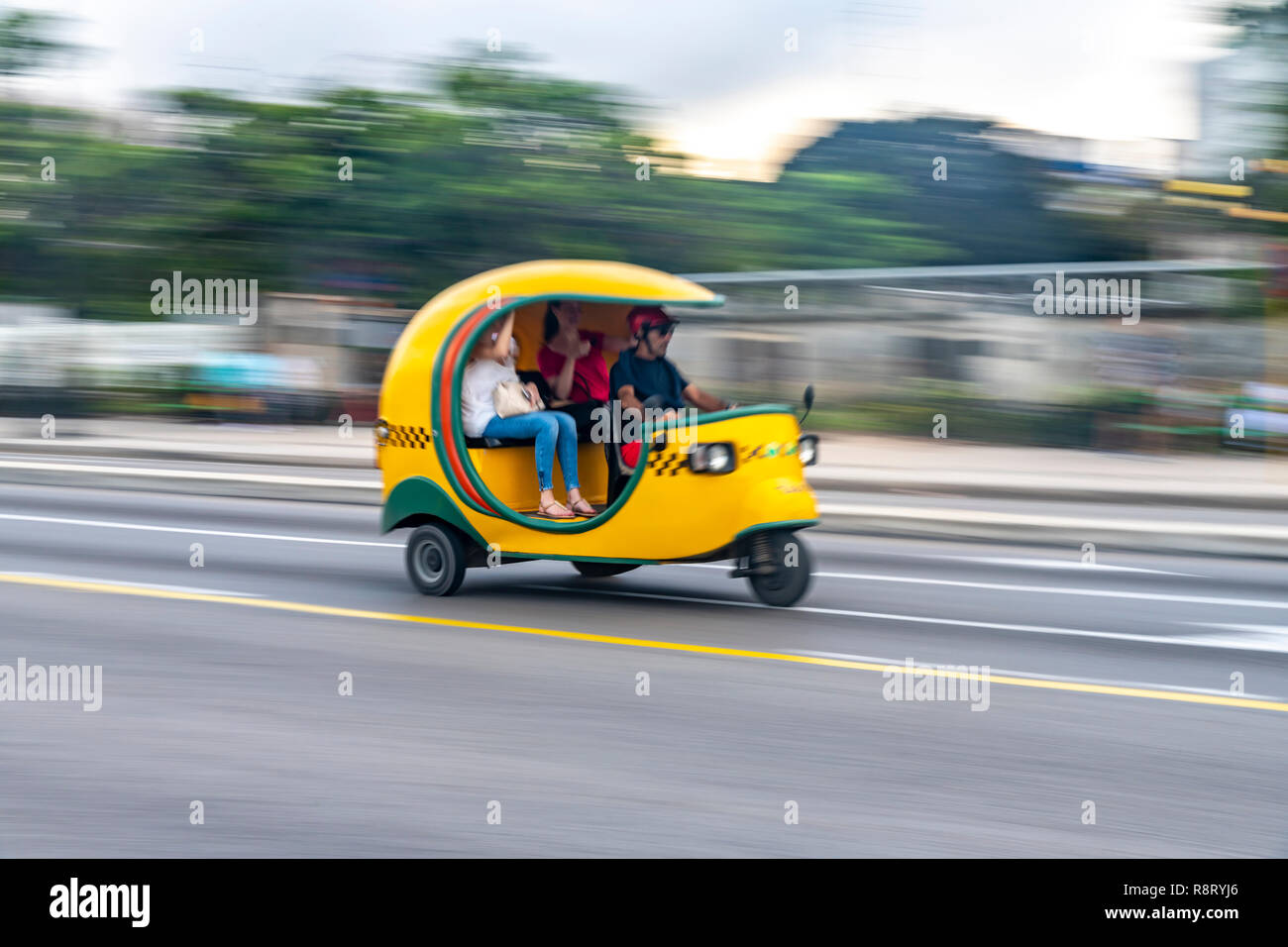 Cuban man driving a speeding bright yellow Coco Taxi with two passengers in Havana Cuba - Stock Image
