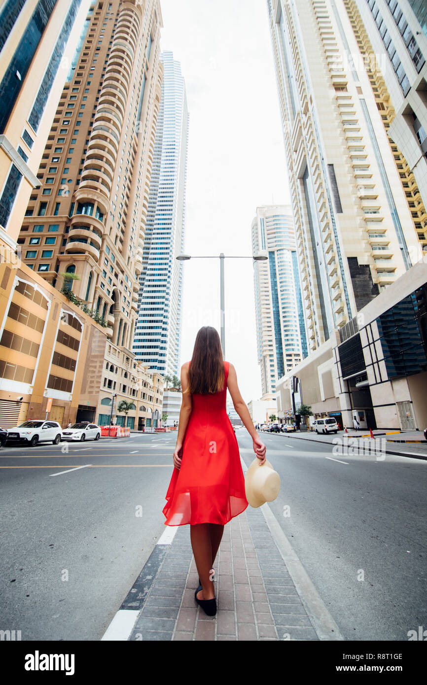 Young woman in red dress and straw hat walking near skycrapers in modern city. Low angle view - Stock Image