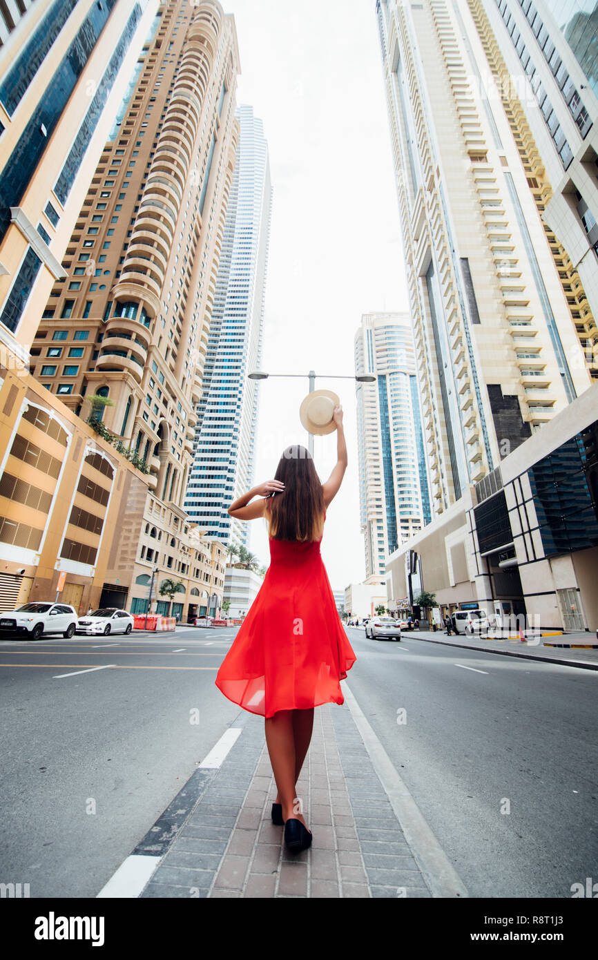 Rear view of young woman in red summer dress holding straw hat while walking near skycrapers on downtown of modern city. - Stock Image