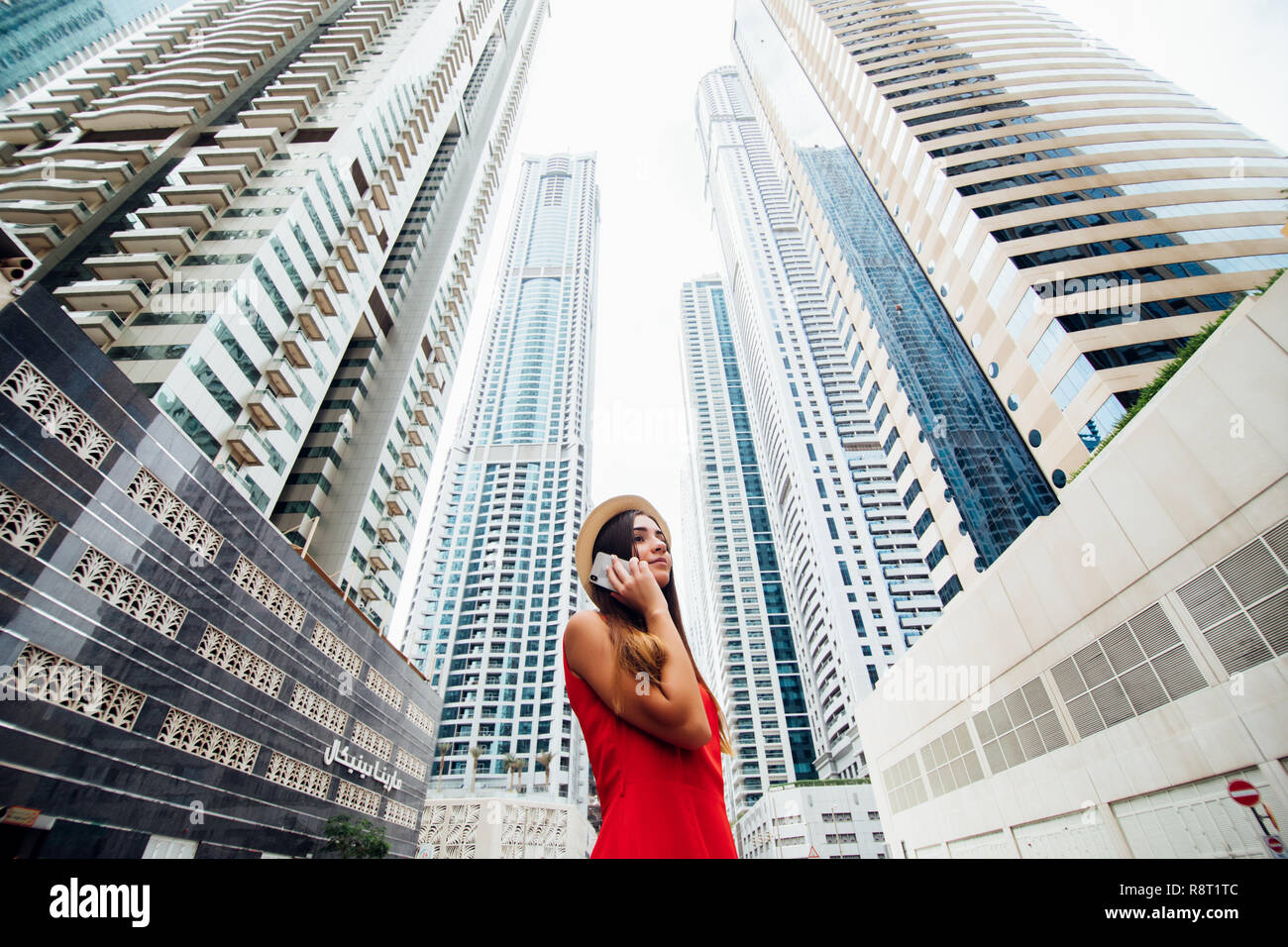 Young woman in red dress and straw hat talking on the phone in front of skycrapers in downtown of modern city. - Stock Image