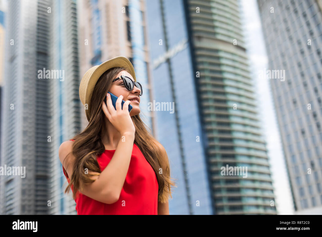 Portrait of young woman in red dress, sunglasses and summer hat talking on the phone on downtown skycrapers background - Stock Image