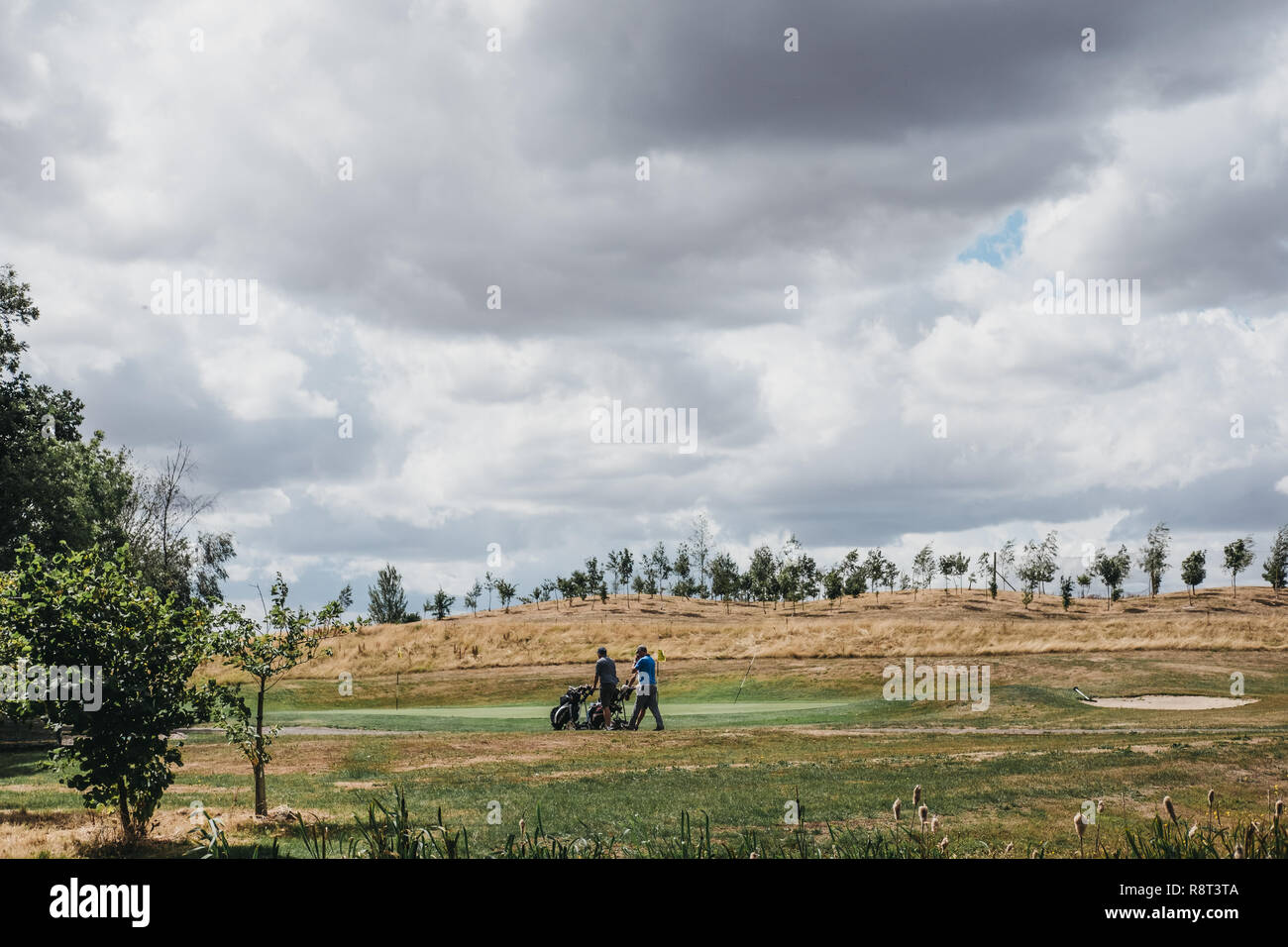 Leicester, UK - July 28, 2018: Two golfers with golf buggies walking across the pitch on the golf course. Golf is a popular sport and leisure activity - Stock Image